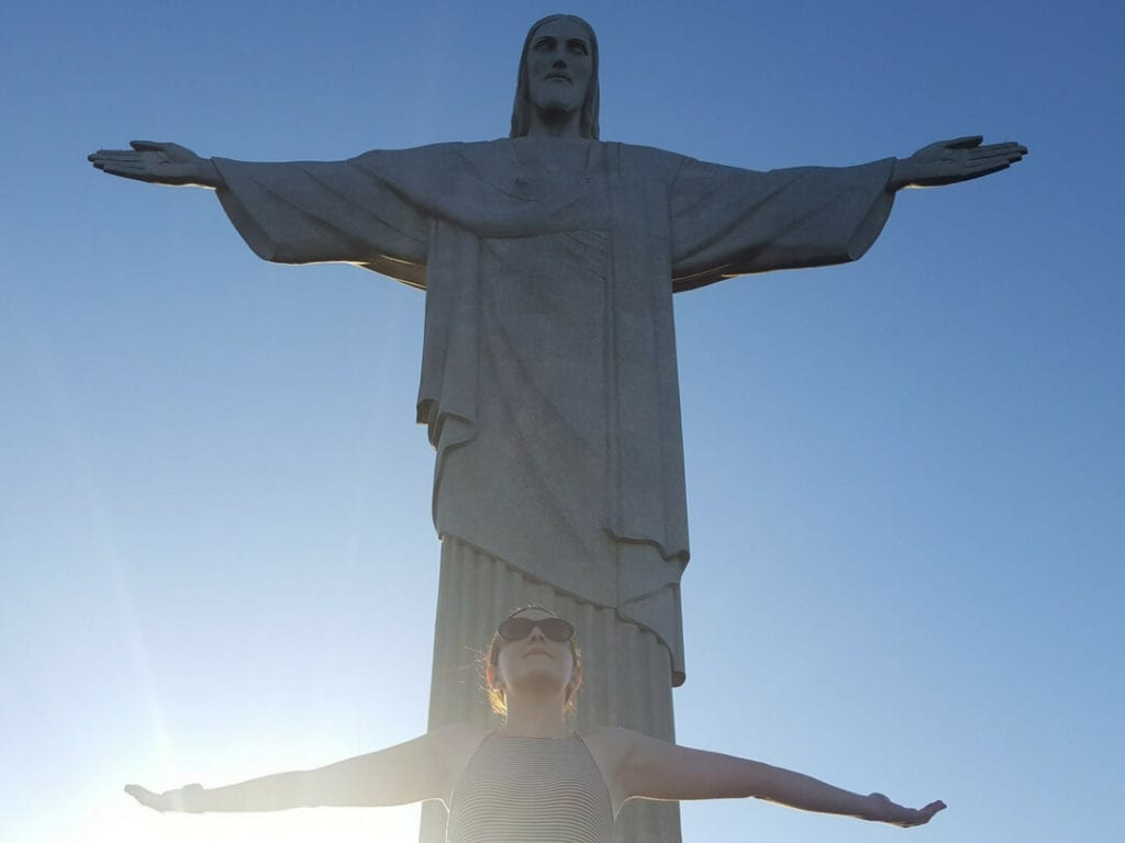 A photo of a woman posing with Christ the Redeemer which is one of the interesting things to do in Rio