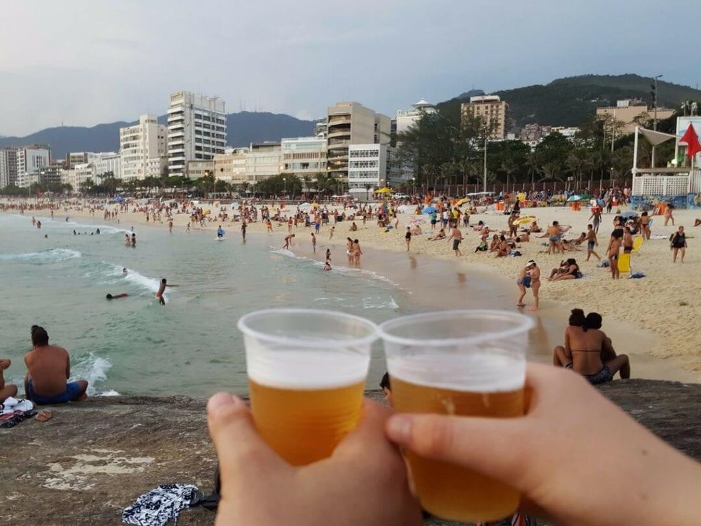 A photo of beers and people at Arpoador Beach, Rio de Janeiro