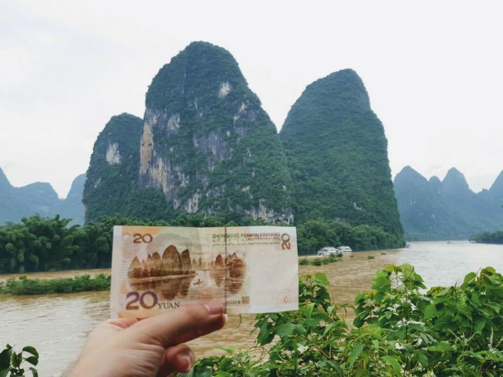 A photo of a 20 Yuan note in front of 20 Yuan note mountain, Yanshuo, guilin mountains, yangshuo mountains,