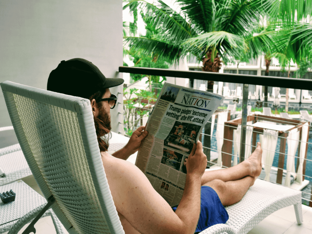 An-image-showing-a-man-reading-a-newspaper-on-a-balcony-in-5-star-luxury-in-Phuket