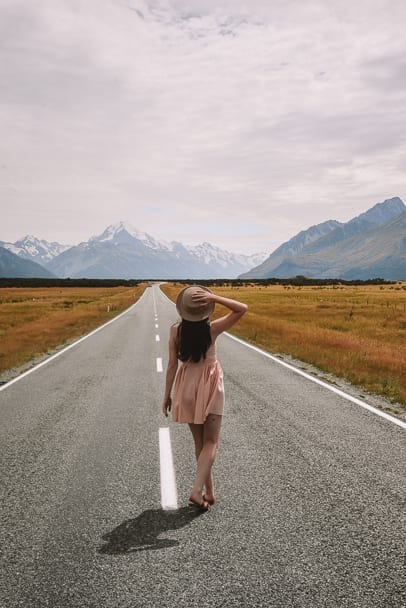 Mt-Cook, Mt-Cook-Road, Mt-Cook-Instagram, Best-Instagram-Places-South-Island-Mt-Cook, girl-crossing-road-pink-dress-mountains-snow-yellow-fields