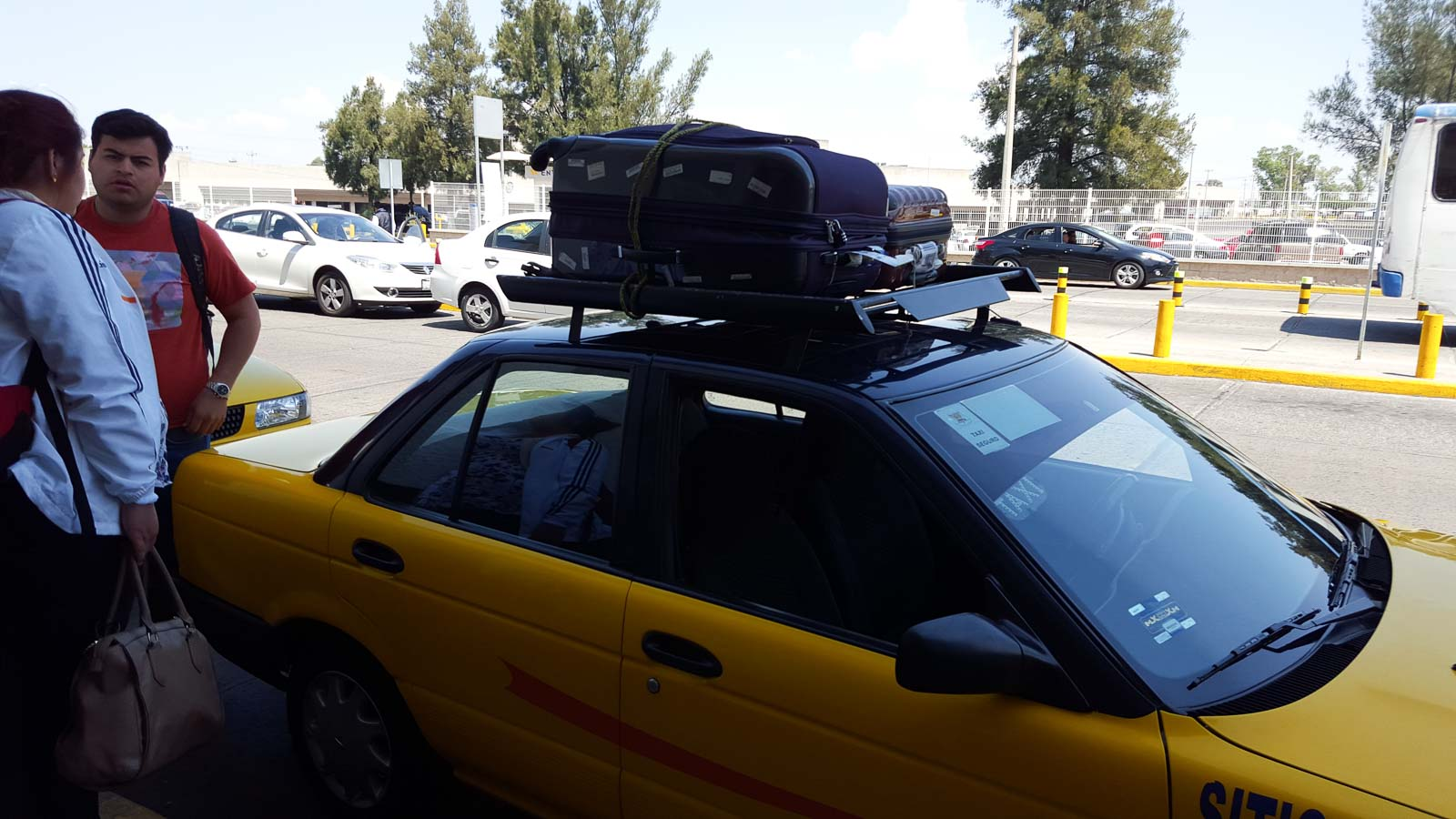 Catching a taxi in Mexico with suitcases on the roof